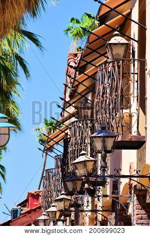 Historic gothic Spanish style building with a row of balconies and lamps taken beside a street