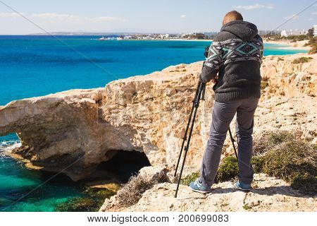 Travel, vacation, photographer and hitchhiker concept - traveler man photographed mountains and town.