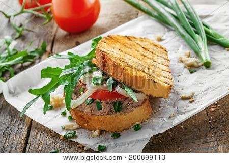 Grilled sandwich with tuna salad tomato onion and arugula on a wooden table. Diet healthy finger food made of toasts vegetables and fish.