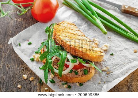 Toast sandwich with tuna tomato onion and arugula. Traditional healthy food made of fish vegetables and grilled bread. Top view.