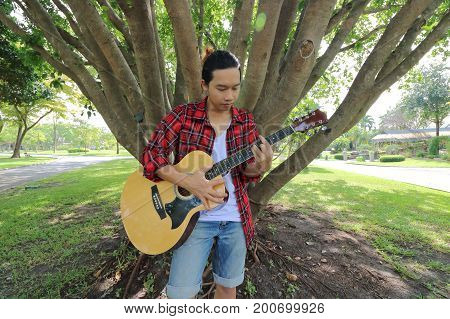 Wide angle shot of young hipster man playing music on acoustic guitar in a beautiful nature background.