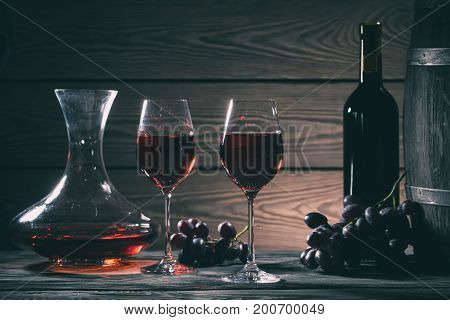 Wine still life with glasses, decanter and bottle on a wooden table. Toning.