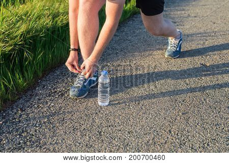 Sport and running idea concept. Young man runner tying shoelaces.