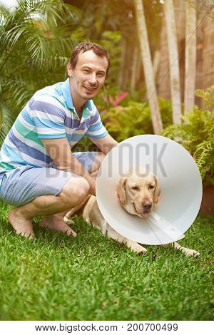 Young man with labrador dog in cone collar