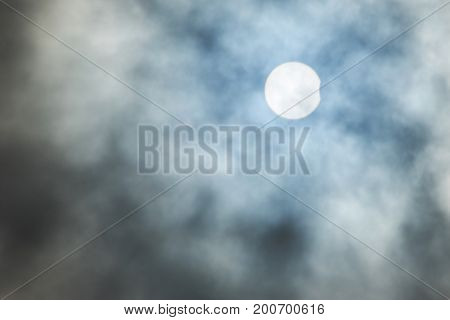 Sun partial eclipse theme on cloudy moody sky background