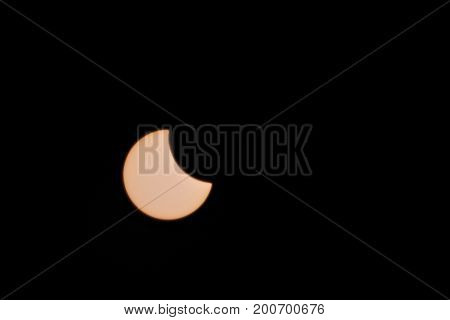 Partial solar eclipse isolated on black background