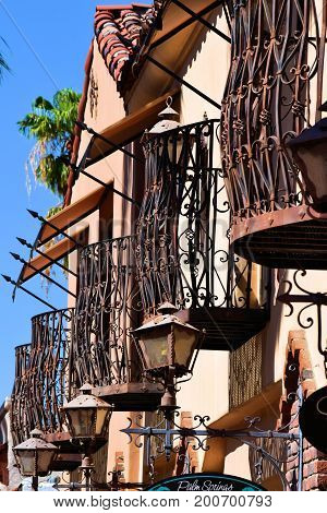 August 9, 2017 in Palm Springs, CA:  Spanish style building with balconies which includes residential and office space above retail stores taken in Downtown Palm Springs, CA where people can dine and shop amongst historic Spanish architectural design