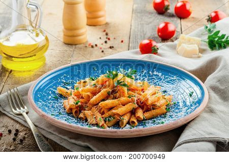 Delicious Italian penne pasta with tomato sauce and parsley on a blue plate. Traditional healthy Italian cuisine meal on a rustic wooden table.