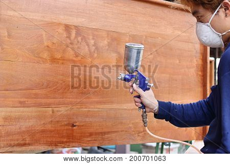 Selective focus on hands of industrial painter with safety mask painting a wooden furniture with spray gun in home workshop. Shallow depth of field.