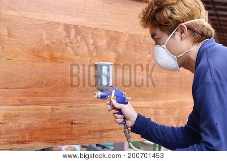 Selective focus on hands of young Asian worker with safety mask painting a piece of wood with spray gun in home workshop. Shallow depth of field.