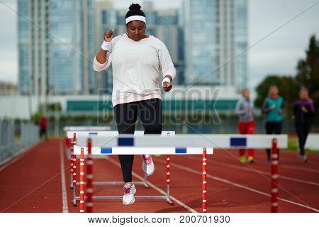 Overweight female running over hurdles on stadium