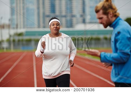 Young obese woman taking part in running marathon