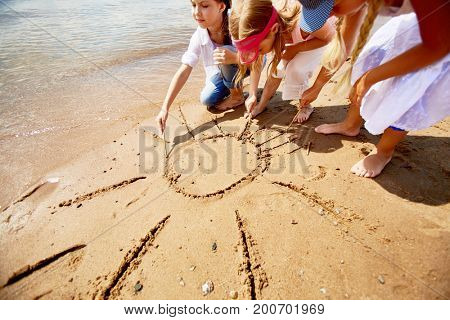 Friendly girls drawing sun on sand by waterside on hot summer day