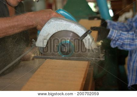 Electric circular saw is being cut a piece of wood againt hands of worker in carpentry workshop.