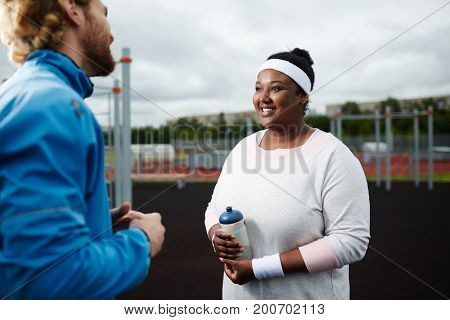 Happy young over-sized woman talking to her trainer at sports ground