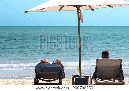 A Couple relax on their beach chair next to the sea for their vacation