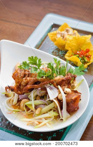 Thai spicy salad with deep fried soft shell crab and sliced green mango Yum Pu Nim in Thai cuisine