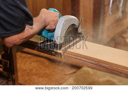 Electric circular saw against sawdust is used by hands of senior carpenter in carpentry woodshop.
