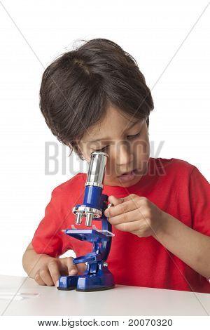 Little boy looking through a microscope