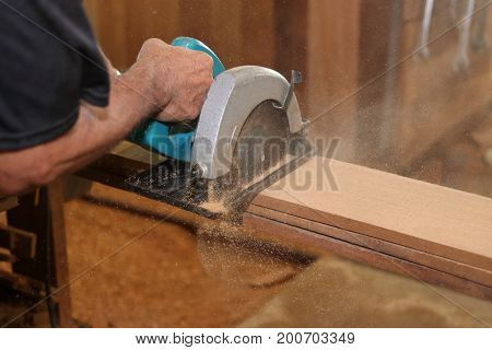 Industrial worker using circular miter saw for cutting wooden boards in carpentry workshop.