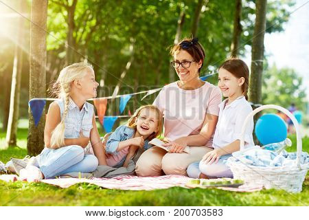 Group of little girls and their teacher discussing tales from book at leisure