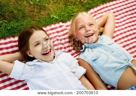 Healthy girls laughing while relaxing at picnic outdoors