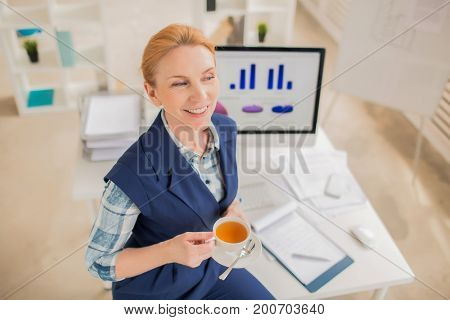 Attractive blond-haired designer looking away with charming smile while enjoying herbal tea in spacious office, high angle view