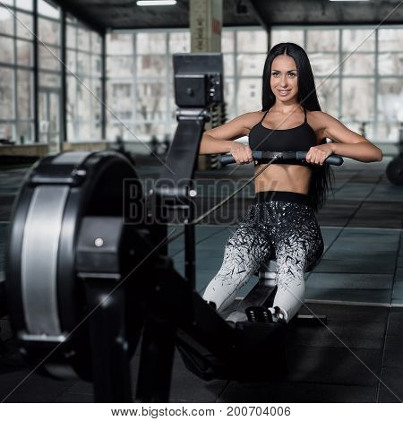 Powerful attractive muscular woman trainer do workout on indoor rower at the gym.
