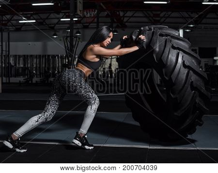 Powerful attractive muscular girl engaged in training with giant tires in the gym. The athlete pushes a large wheel. Exercise with heavy weight in the gym.