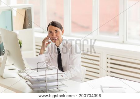 Waist-up portrait of cheerful Asian white collar worker conducting telephone negotiations with business partner while sitting at desk in spacious office
