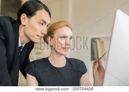 Multi-ethnic group of white collar workers analyzing results of accomplished work with help of computer, blurred background