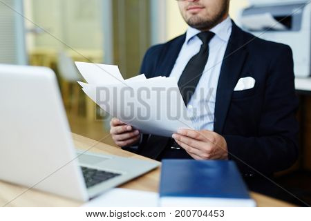 Economist in suit holding papers in hands and reading them at work