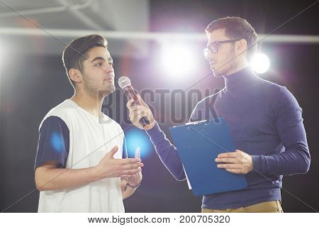 Profile view of handsome bearded lecturer holding microphone in hand while communicating with audience