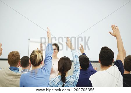 Enthusiastic group of students sitting in classroom with raised hands, their teacher looking at them with wide smile, rear view