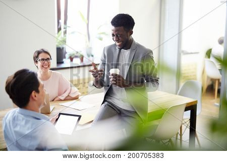 Office workers telling jokes and laughing during coffee break