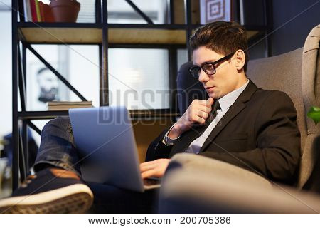 Young specialist with laptop searching for job in the net