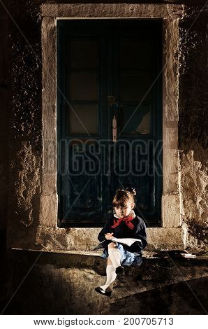 Little caucasian schoolgirl sitting in the nightstreet and doing the exercises beneath the lamplight.