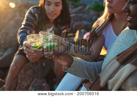 Two girls and guy toasting with glasses of refreshing cocktail