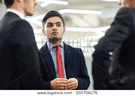 Portrait shot of handsome young white collar worker listening to his male colleague with interest while having project discussion at office lobby, low angle view