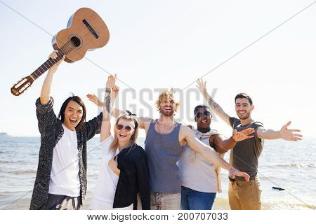 Ecstatic young people with guitar raising their hands on background of water