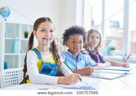 Clever girl and her classmates sitting at lesson in elementary school