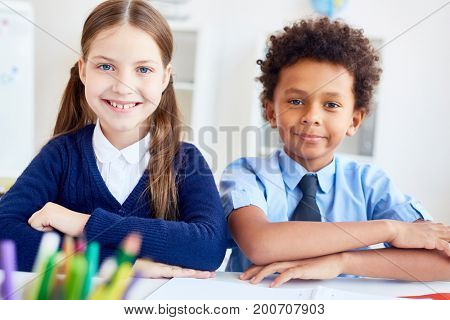 Intercultural schoolkids sitting by desk at lesson