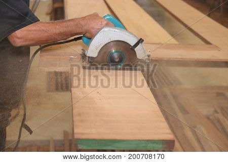 Electric circular saw against sawdust is cut a piece of wood by hands of senior carpenter in carpentry woodshop.