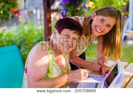 Toothy smile from teenage grandchild and retired granny after learning to use laptop technology and internet.