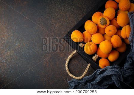 Delicious ripe apricots on a wooden stand on a dark black background. Selective focus. Top view. Cope space.