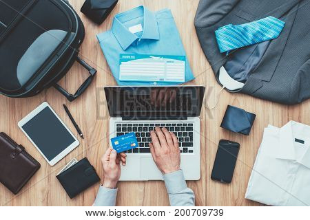 Corporate businessman packing his bag and planning a business trip he is booking flights online using a laptop and a credit card travel and technology concept