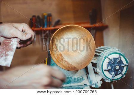 Wood turners using sandpaper polished wood on a lathe