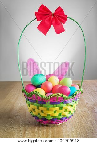 multicolored Easter eggs in the wattled basket on vintage wooden table