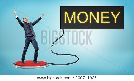 A victorious businessman stands on a large red pushbutton that's connected to a monitor with a word MONEY. Lottery winner. Luck and fortune. Business and success.