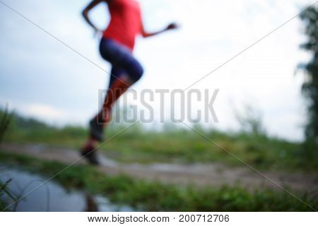 Blurred photo of running girl on path in park